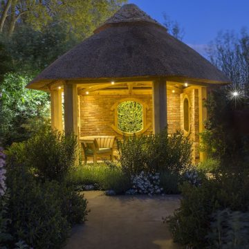 Garden Lighting. Wooden chair in thatched summerhouse lit at night. Bespoke Summerhouse hand-crafted from Oak