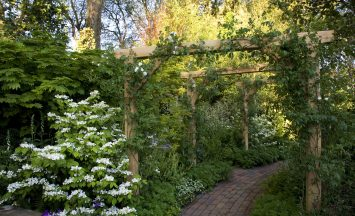 Oak Pergola Garden arch over pathway in Traditional English Garden at The Chelsea Flower Show designed by Roger Platts