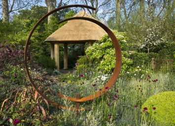 View through circular Cor-Ten steel sculpture to thatched summerhouse, Cirsium rivulare 'Atropurpureum', Cornus kousa var. chinensis 'China Girl'